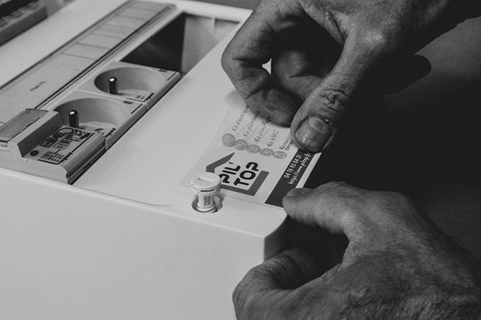 Equipier Pil Top en train de finir un tableau électrique dans l'atelier